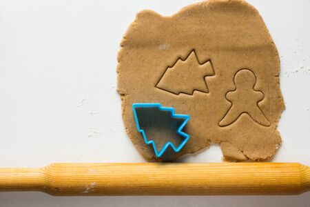 Cutted form of christmas tree and man on rolled out gingerbread dough on the white background