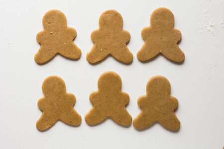 Cut out gingerbread men on the white background before baking