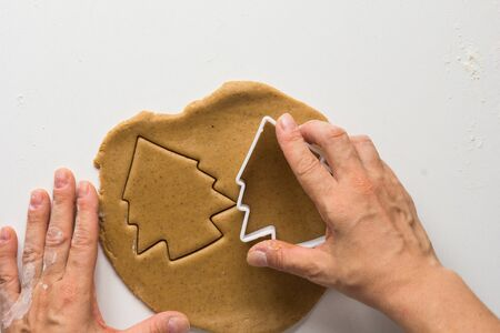 Woman hands cutting forms of christmas tree on rolled out gingerbread dough on the white background 写真素材