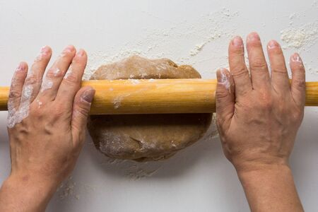 Woman hands rolling out gingerbread dough by rolling pin on the white background 写真素材