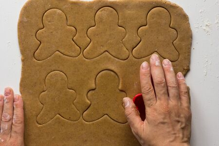 Woman hands cutting forms of man on rolled out gingerbread dough on the white background