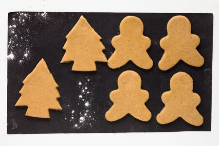 Cut out gingerbread men and christmas tree on the black background before baking 写真素材