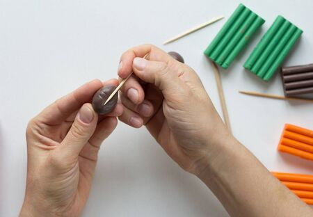 Woman hands making strips with tooth stick on brown ball from polymer clay for create potato