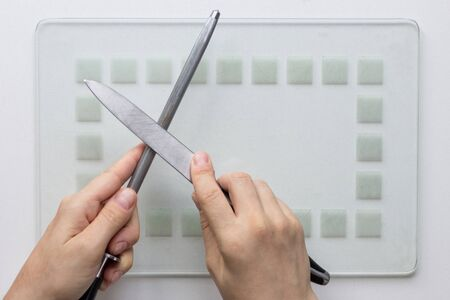 Knife and sharpener in woman hands sharpening on the white background