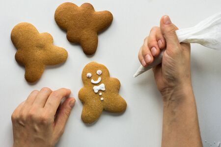 Baked gingerbread cookies men decorated with icing by woman hand on the white background 写真素材