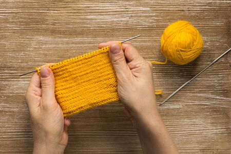 Woman hand holding knitting pattern wrong side by yellow yarn on the wooden background 写真素材