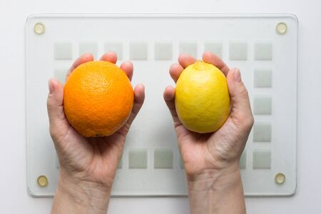 Ripe orange and lemon in woman hands on the white background 写真素材