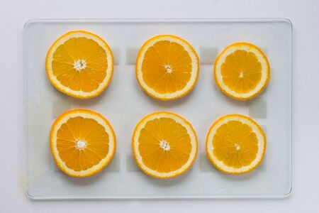 Cutted orange on glass cutboard on the white background 写真素材