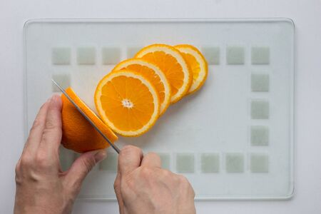 Woman hand cut orange with knife on the white background 写真素材