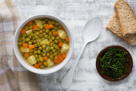 Soup with green peas and vegetables in white bowl on the white background