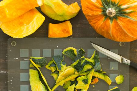 Stripes on glass cutting board after peeling pumpkin on wooden background
