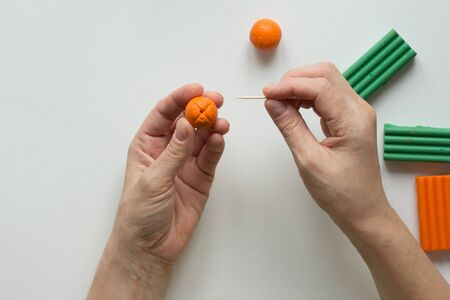 Woman hands showing dot on orange ball made by tooth stick to create orange fruit from polymer clay