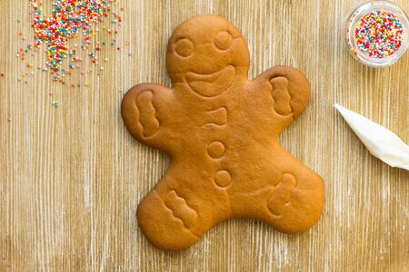 Baked gingerbread cookie man before decoration on wooden background