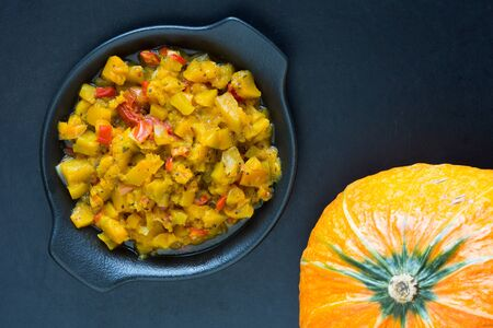Homemade pumpkin stew with vegetables on black background