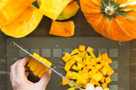 Cutting piece of pumpkin with kitchen knife by woman hand on glass cutting board on wooden background