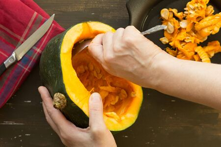 Cleaning out pumpkin with spoon by woman hand on wooden background