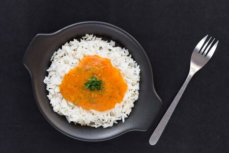 Rice with pumpkin sauce on black plate on black background