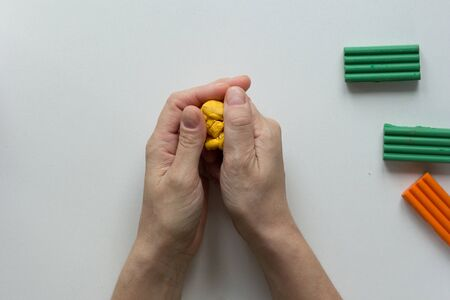 Woman hands making soften and warm piece of polymer clay on the white background 写真素材