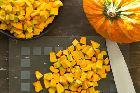 Cutted pieces of pumpkin on glass cutting board on the wooden background