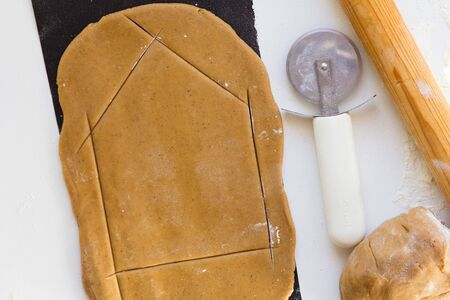 Cutting out wall of gingerbread house with knife for pizza on rolled raw gingerbread