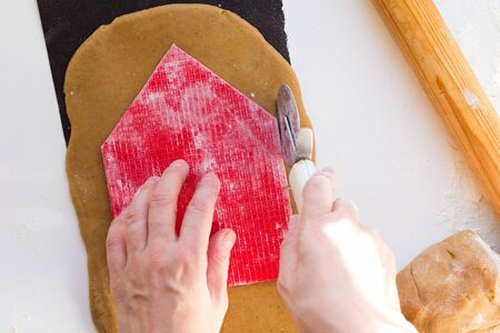 Woman hands cutting out with knife for pizza a wall of gingerbread house using homemade form for gingerbread house on rolled raw gingerbread dough on black baking sheet on white background.