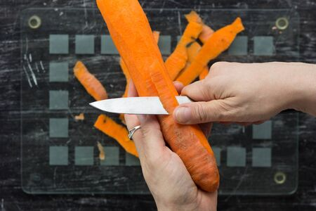 Top view of woman hands peeling carrot with knife on glass cutting board on black background