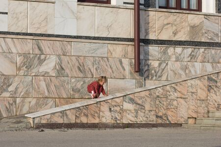 Caucasian child of two years old trying to climb on marble fence near building putting feet on it