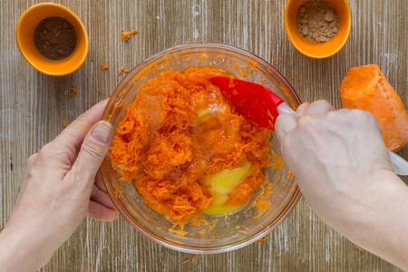 Woman hands mixing batter for carrot pie on wooden background