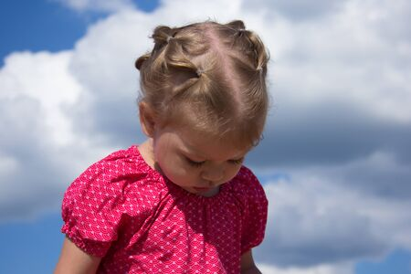 Bowed head of caucasian child of two years old walking on blue sky background in summertime