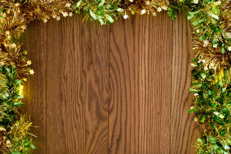 Wooden background along the edge with tinsel. Christmas background
