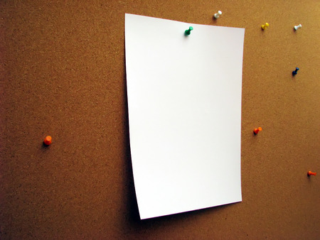 corkwood: Sheet of paper on corkwood board fixed by green pushpin.