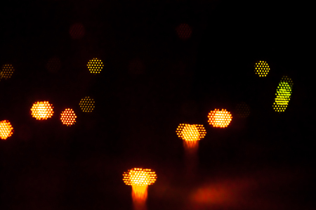 Blurred street lights through black window net