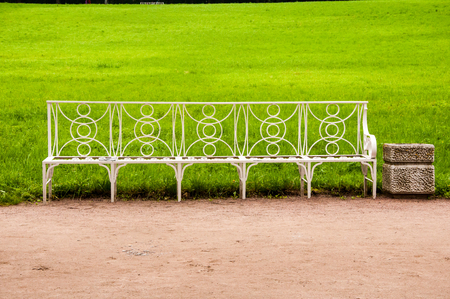White metal bench in the park with green lawn