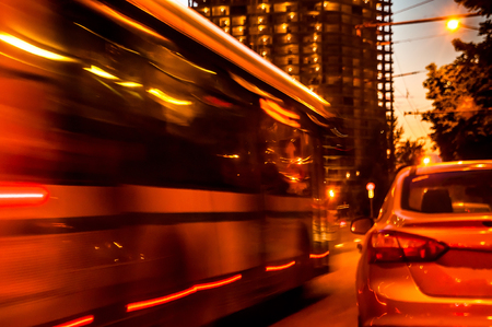 unfinished building: A blurred moving bus in the sity on sunset