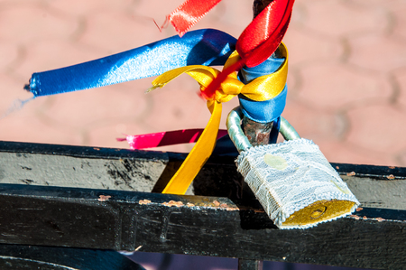 closed ribbon: A wedding padlock with bright ribbons on the black fence Stock Photo