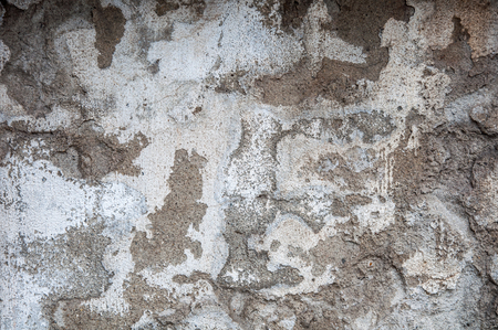 Texture of an old wall covered with spots of grey relief plaster