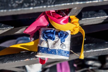 door lock love: A padlock coiled with white and blue ribbons and decorated with handmade roses Stock Photo