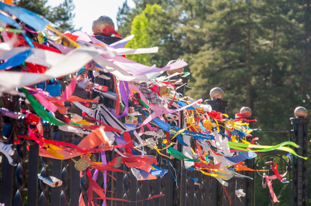 The plenty of bright ribbons on the black fence waving in the wind which people tie for luck Stock Photo - 82119078