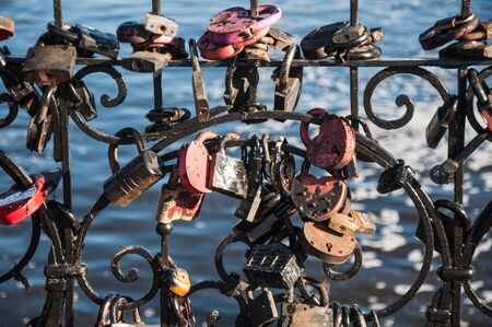 A lot of wedding padlocks of different sizes and shapes on the curved cast-iron black grate on the background of blue water Stock Photo