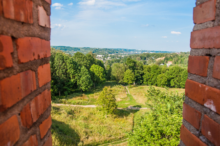 A view from the loophole in the ancient fortress at the park and city