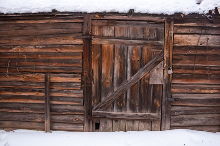 A general view at the wall and door with locked padlock of an old wooden house in the Russian countryside. Winter.