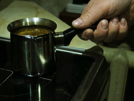 Coffee making time. Man leisure and lifestyle. Hands with jezve pouring latte into red cup. Stok Fotoğraf