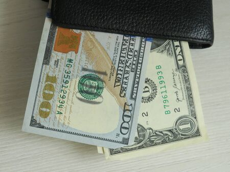 pulling focus on a folded and very used wallet with cards and cash inside on a table with a blurry background