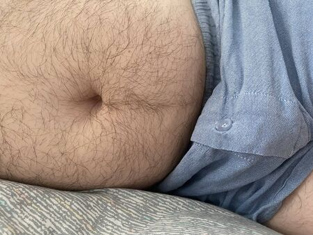 Funny fat man showing his big belly. He puts a hand on the belly