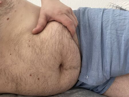 Funny fat man showing his big hairy belly.