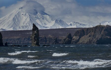 Lighthouse on coast of Pacific Ocean. Russian Far East, Kamchatka Peninsula, Petropavlovsk-Kamchatsky City. Lighthouse on the Stanitskiy Cape with Viluchinskiy volcano on the background. Picturesque place, seascape. Storm sea