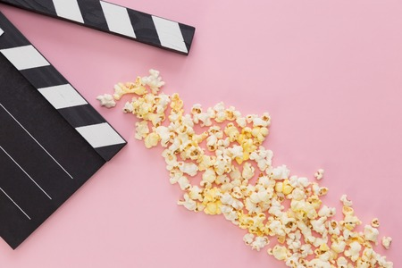 black clapperboard and popcorn with free space for text isolated on color background