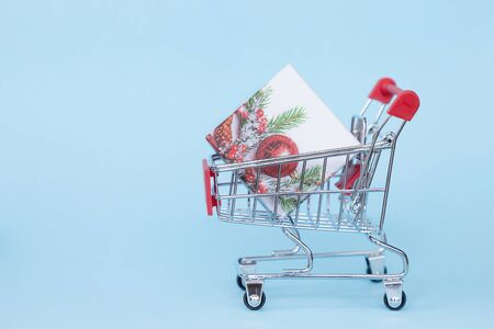 Christmas gifts in a supermarket trolley on a blue background