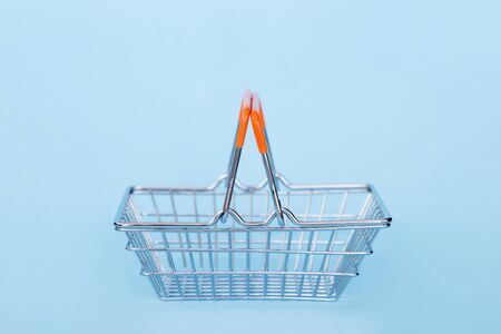 Empty grocery cart on wheels on a blue background
