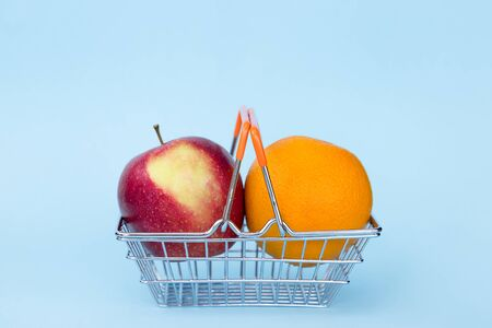 red apple fnd orange in grocery cart on blue background